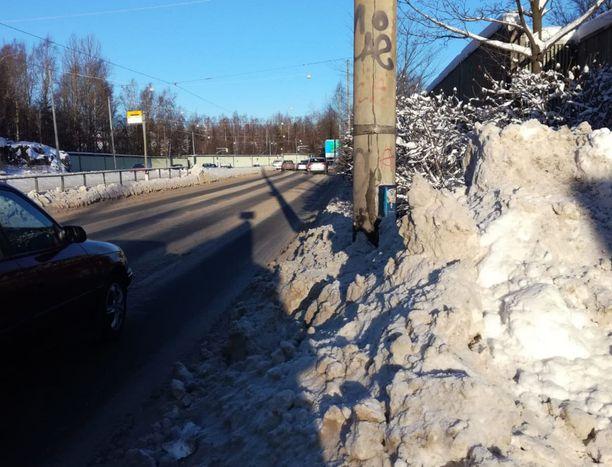 Lumi hankaloittaa itsestäänselvinä pidettyjä toimia, kuten kuvassa lumikinoksen takana näkyvän jalankulkijoiden liikennevalonapin painamista.