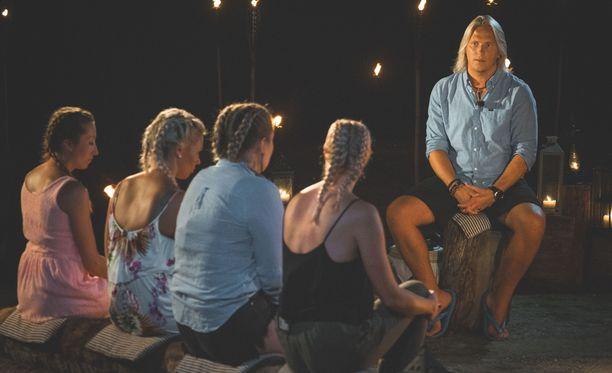 Sami Kuronen hiillostaa, naiset istuvat pölkyllä letit päässä kuin koulussa ikään.