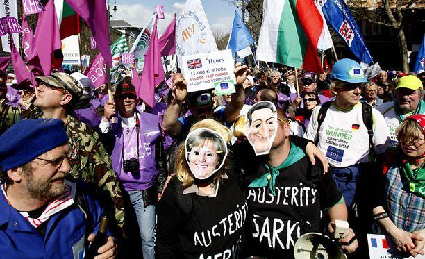 Mielenosoittajilla oli Angela Merkeliä ja Nicolas Sarkozya kuvaavat naamarit.