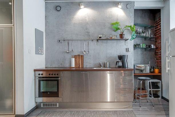 Teollisuushenkiseen keittiöön on valittu teräskaapit ja ruskea työtaso. Yllättävä yhdistelmä toimii!