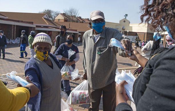 Hyväntekeväisyysryhmä jakamassa ruokaa ja tarvikkeita kansalaisille Soweton alueella Johannesburgissa.