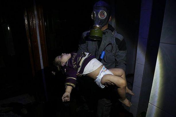 Pelastustyöntekijä kantoi kemiallisten aseiden iskun uhriksi joutunutta lasta Doumassa viikonvaihteessa.