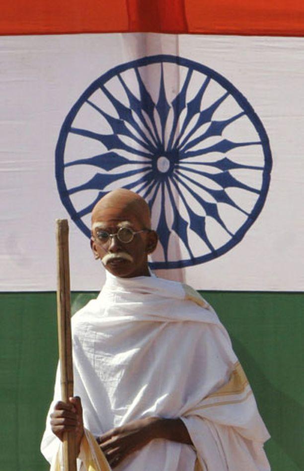Mahatma Gandhi kuoli yli 60 vuotta sitten. Kuvassa patsaan takana Intian lippu.