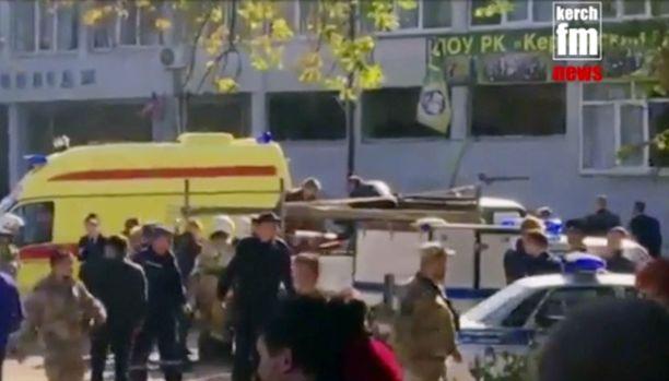 Pelastajat kuljettivat haavoittuneita koululta Kertshissä keskiviikkona.