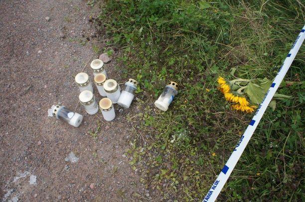 Poliisin sulkunauhalle tuodut kynttilälyhdyt ja kukat muistuttivat järkyttävästä veriteosta.