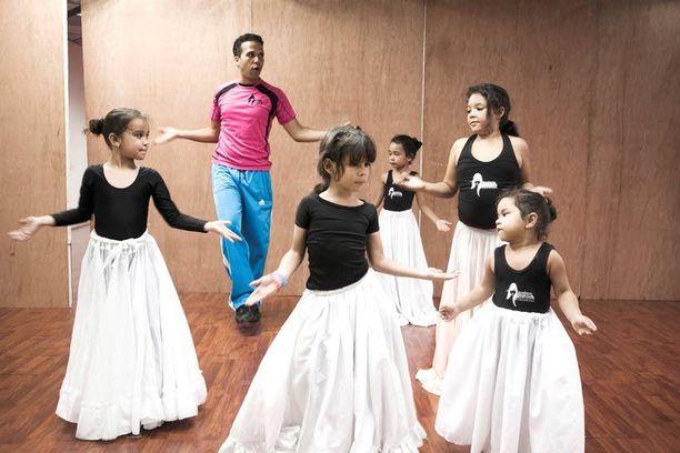 Mallikoulun pikkutytöt opettelevat tanssimista pitkät hameet päällään.