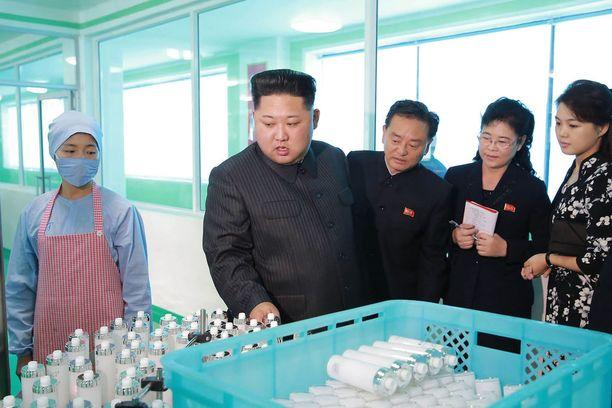 Kim Jong-un tutkaili kosmetiikkapurtiloita tehtaalla. Kuvassa oikealla mustavalkoisessa mekossa vaimo Ri Sol-ju.