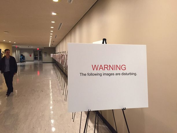 Kyltti varoittaa raaoista kuvista YK:n päämajassa New Yorkissa.