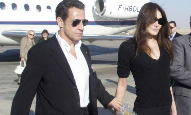 Tylystä ilmeestään huolimatta Sarkozy piti uutta kultaansa kädestä.