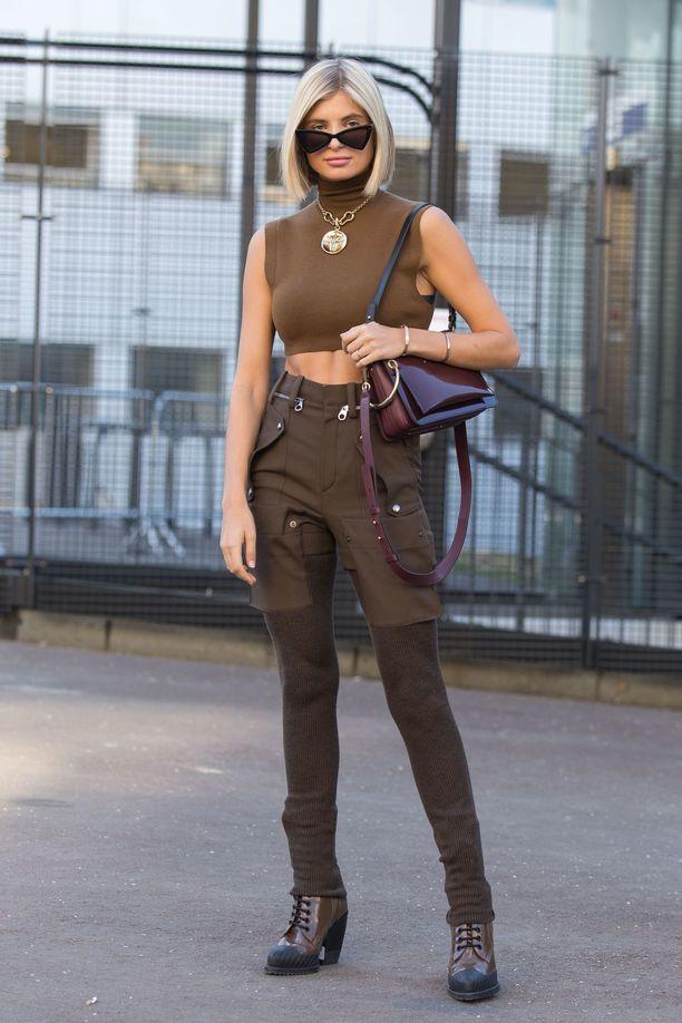 Xenia Adontsin ruskeassa asussa on muitakin muodikkaita elementtejä kuin väri: kultainen kaulakoru, kissamaiset lasit ja cargo-housut ovat kaikki kesän 2019 suosikkeja.