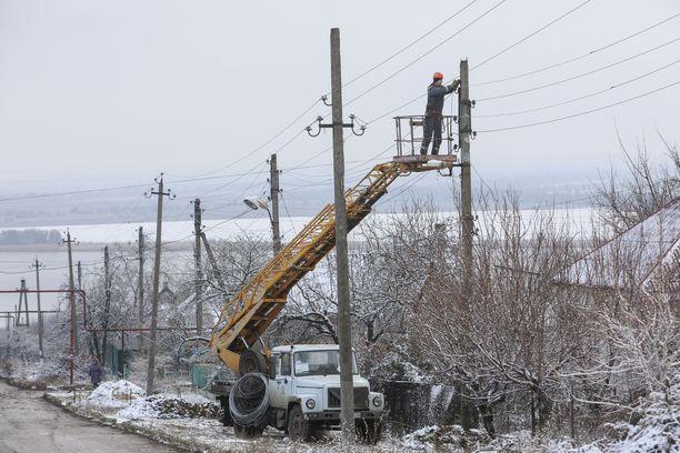 Ukrainalaistyöntekijät korjaavat taisteluissa vaurioituneita sähkölinjoja Donetskin alueella. JCCC pyrkii varmistamaan tulitauon juuri tällaisten korjaustöiden ajaksi. Kuva joulukuulta 2017.