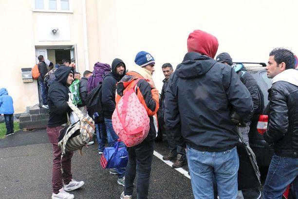Linja-autoilla Luulajasta tulleet turvapaikanhakijat järjesteltiin odottamaan rekisteröitymistä vanhan lukion ovelle.