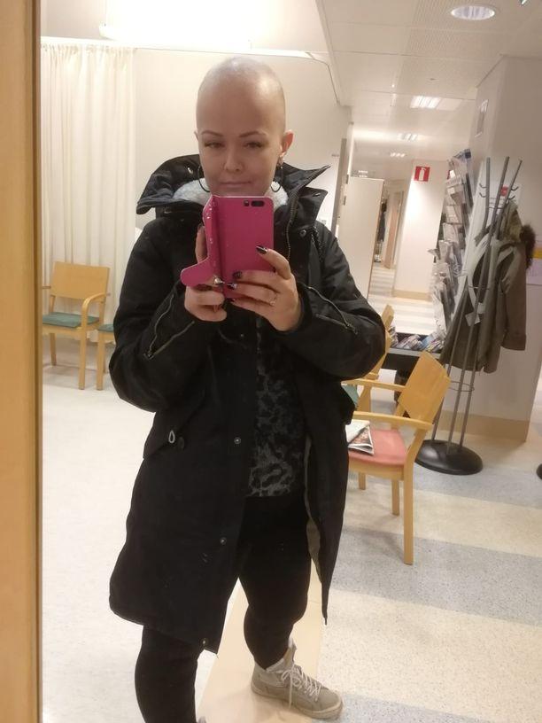 Kuvassa Janiina Hill sairaalassa. Hiusten, ripsien ja kulmien menetys oli hänelle kova paikka, mutta iloa hän sai esimerkiksi isoista korvakoruista.