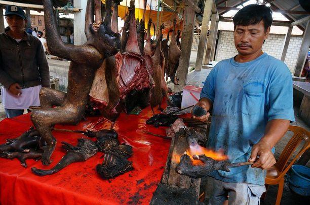 Torikauppias grillasi sulawesinmakakin ruumiinosia torilla Pohjois-Sulawesilla vuonna 2014.