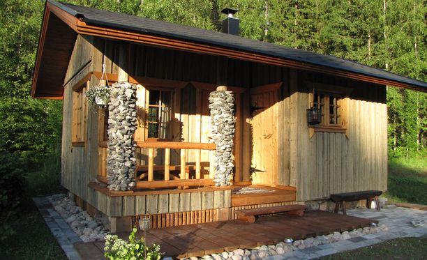 """4. Omin kätösin rakennettu """"Sauna on valmistunut keväällä 2012 ja se on mieheni itse rakentama alusta asti. Sauna ja sanakammari ovat tumman savusaunamaisia ja hämyisiä. Korkealla on """"isännän"""" omat lauteet ja kiukaan takana luonnonkivistä muurattu seinä. Rypsipellon laidassa saunominen ja pulahtaminen vieressä olevaan altaaseen uimaan on parasta kesässä."""""""