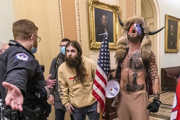 Tällaisissa tamineissa Jacob Chansley (kuvassa oikealla) esiintyi kongressitalossa loppiaisena. Myöhemmin hänet kuvattiin muun muassa istumassa varapresidentin paikalla senaatin istuntosalissa.