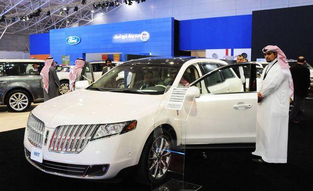 Ostajat ihastelemassa autoja autonäyttelyssä Riadissa. Pian myös naiset pääsevät maassa auto-ostoksille.