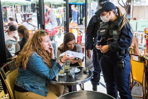 Poliisit tarkastivat ihmisten koronapasseja maanantaina Pariisin kahviloissa ja ravintoloissa.
