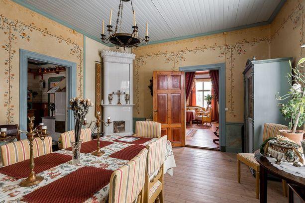 Talonpoikaistyyliset seinämaalaukset tuovat persoonallista ilmettä. Ruokatilan kulmauksesta löytyy perinteinen kakluuni.