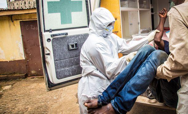 Sairaalatyöntekijä auttoi ebolapotilaan siirtämisessä Sierra Leonessa.