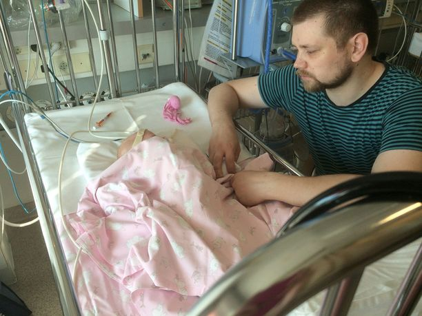 Uupunut isä Arttu Pätäri leikkauksesta toipuvan lapsensa vieressä. Lapsi joutui odottamaan isoa leikkausta pitkään resurssipulan vuoksi.