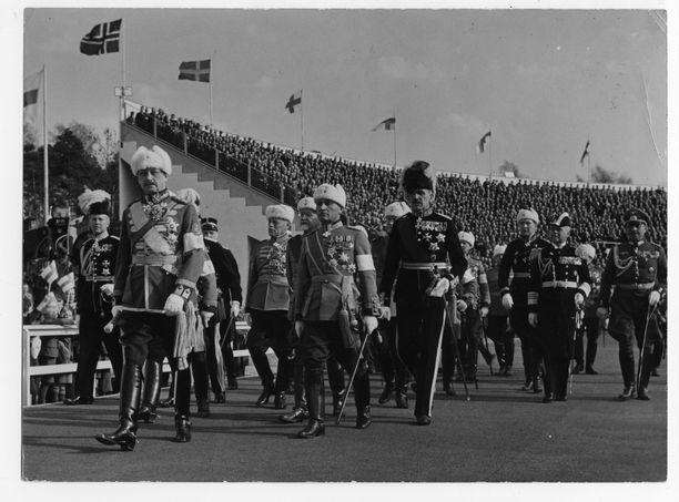 Mannerheim seurueineen saapuu vasta valmistuneelle Helsingin olympiastadionille puolustusvoimain lippujuhlanpäivän paraatiin 16. toukokuuta 1938. Valkoiset hihanauhat näkyvät käsivarsissa.