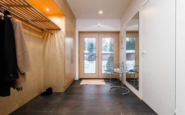 Valoisaan eteiseen on tuotu säilytystilaa koko seinän kattavan vaatesäilytysjärjestelmän avulla. Takeille ja kengille riittää tilaa, ja myös vieraat saavat takkinsa ripustettua vaivatta.
