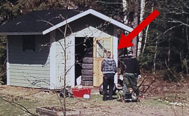 Salakuvassa kaksi siviilipukuista poliisia penkoo Jari Aarnion naapurin ulkovarastoa.