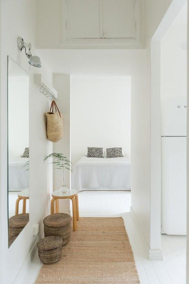 Seesteinen, hillityin sävyin sisustettu käytävä johdattaa harmoniseen makuuhuoneeseen. Luonnonmateriaalit ja valkoinen rauhoittavat.