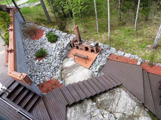 Kesäkeittiön ei välttämättä tarvitse olla katettu. Tämän rantakalliolla sijaitsevan talon pihaan on muurattu pieni kesäkeittiö.