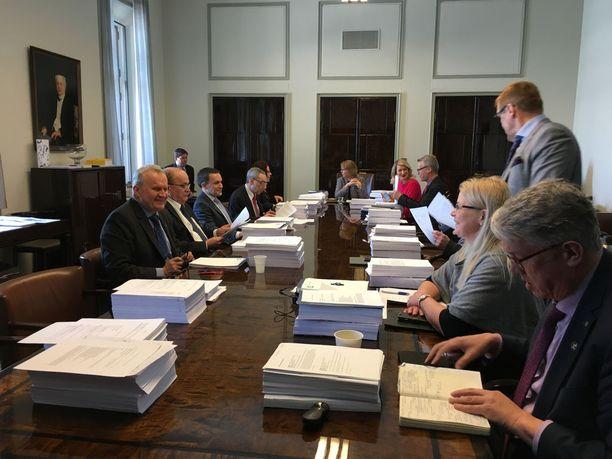 Eduskunnan perustuslakivaliokunnan jäsenet saivat eteensä tuhdin pinkan paperia. Pöydän päässä valiokunnan puheenjohtaja Annika Lapintie.