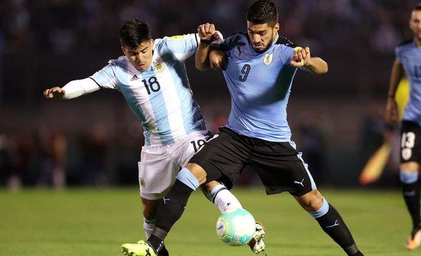 Luis Suarez (9) väänsi Marcos Acuaan kanssa Uruguayssä.