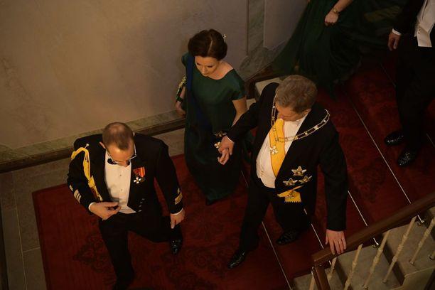 Presidenttipari siirtyy adjutantin johdolla Linnassa tilasta toiseen. Näin hellästi käsi kädessä Sauli Niinistö astelee vaimonsa kanssa portaikossa.