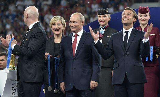 MM-mitaleita jakamassa ollut nainen (toinen vas.) sujautti yhden kultamitalin taskuunsa.