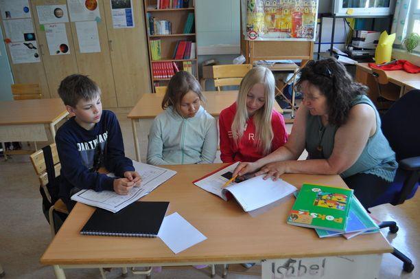 Lumparlandin koulun oppilaat Kalle, Jasmin ja Isabel uskovat, että heille on hyötyä suomen taidosta tulevaisuudessa. Jasmin on oppinut suomea kotona isältään, kun taas Kalle ja Isabella aloittivat suomen opiskelun alusta viidenneltä luokalta. Kuvassa myös suomen opettaja Anne Hämäläinen.