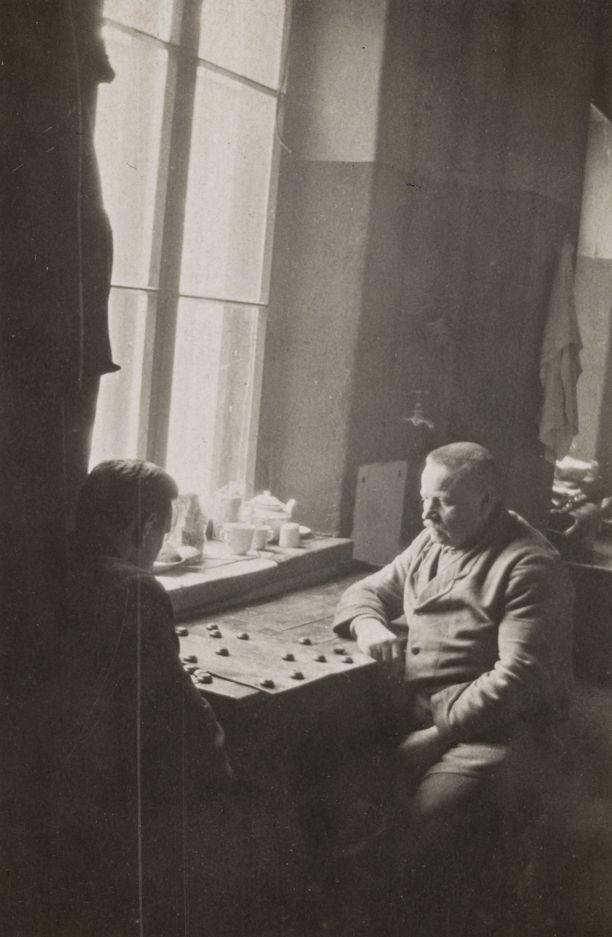 Poliisi pelaa Tammi-peliä vangin kanssa poliisiaseman sellikäytävällä helmikuussa 1918 sisällissodan aikaan.