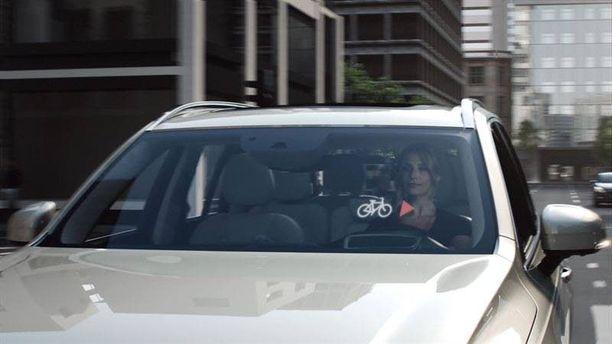 Auton tuulilasiin ilmestyy polkupyörän kuva, kun kypäräpää lähestyy ns. pimeästä kulmasta.