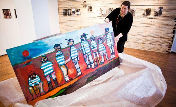 Galleriatyöntekijä Marianne Ikävalko purkaa Anssi Hanhelan taideteoksia Galleria Napassa. Kuvassa porua herättänyt teos Markkinavoimat.