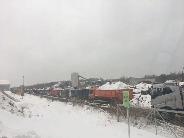 Tähän kuvaan tiivistyy Helsingin lumikaaos. Autot jonottavat kuormineen lumenkaatopaikalle.