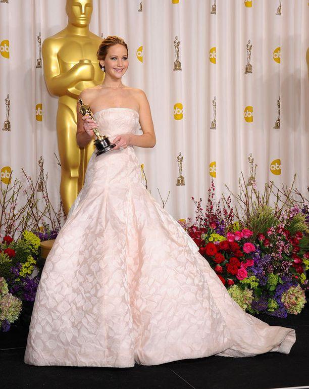 SUOSITUIN Jennifer Lawrencen iltapuvun muhkea helma osoittautui epäkäytännölliseksi portaissa, kun näyttelijätär kompastui hakiessaan parhaan naisnäyttelijän palkintoa. Kaunis asu oli Diorin haute couturea.