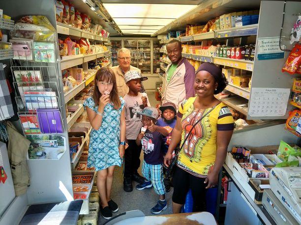 Sallisen myymäläautossa käy vieraita myös kaukaa. Kuvassa kauppiaan kanssa Ghanasta kotoisin oleva perhe, äiti Anette Boakye ja Benjamin Boakye lapsiensa kanssa. Mukana kuvassa myös kauppiaan lapsenlapsi Sini Sallinen.