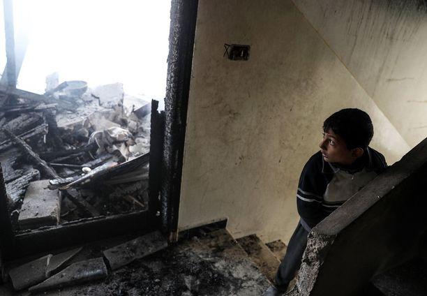 Syyrialaispoika pommitusten tuhoamassa rakennuksessa Doumassa.