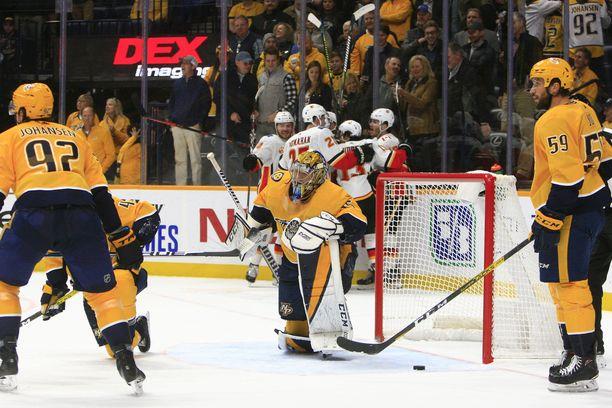 Pekka Rinne keräilee itseään polviasennossa, kun Flamesin pelaajat juhlivat taustalla.