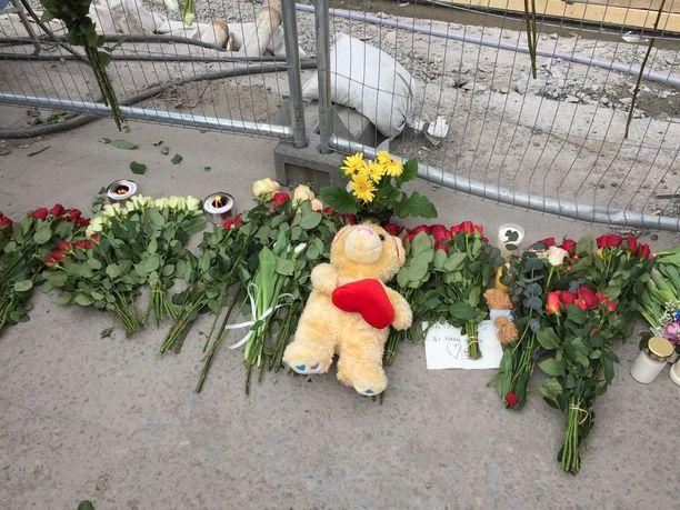 Ihmiset ovat tuoneet paljon kukkia, kynttilöitä ja pehmoleluja Åhlensin tavaratalon ulkopuolelle.