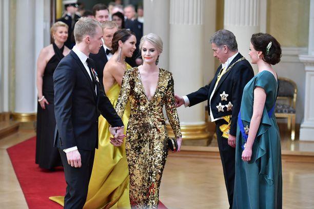 Hiihtäjä Iivo Niskasen puoliso Saana Kemppainen juhli Iivon siskon Katri Niskasen suunnittelemassa kultaisessa.