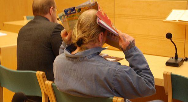 Anna-Emilian surmannut Tommi Taneli Nakari piiloutui lehden taakse vangitsemisoikeudenkäynnissään tammikuussa.
