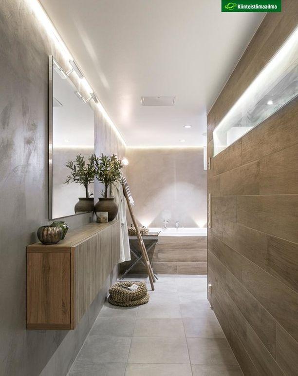 Tunnelmallinen valaistus kylpyhuoneessa tuo heti spa-henkeä ja seesteisyyttä. Huomaa näyttävät valaisimet kylpyammeen takana.
