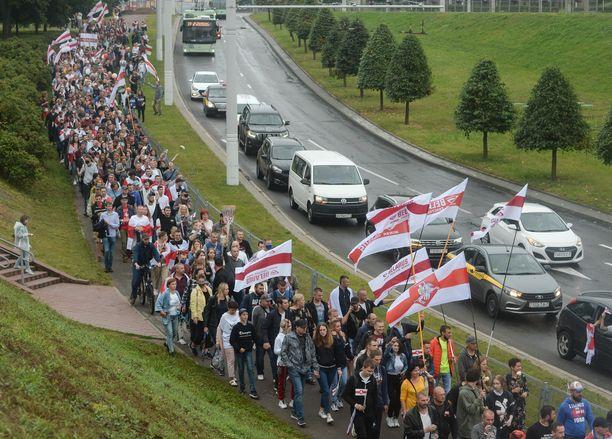 Eri tehtaiden työntekijät marssivat kohti mielenosoituspaikkaa Minskissä sunnuntaina.