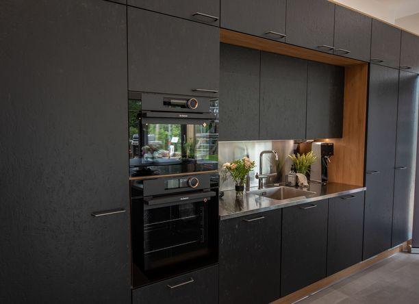 Mustaa rouheaa mattapintaa, puuta ja terästä. Puu tuo keittiön ilmeeseen lämpöä.