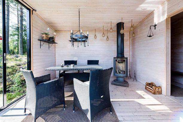 Pihasaunan takkatupaan on valittu polyrottinkiset huonekalut. Valinta on fiksu, sillä ne on helppo pitää puhtaana. Pienet sisustuselementit, kuten hauska puinen kori, tuovat pihasaunaan hieman persoonaa.
